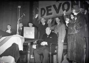 Plymouth Devonport election, 1950. Winston Churchill sat by ballot box with dignitaries. © Plymouth Arts and Heritage Service